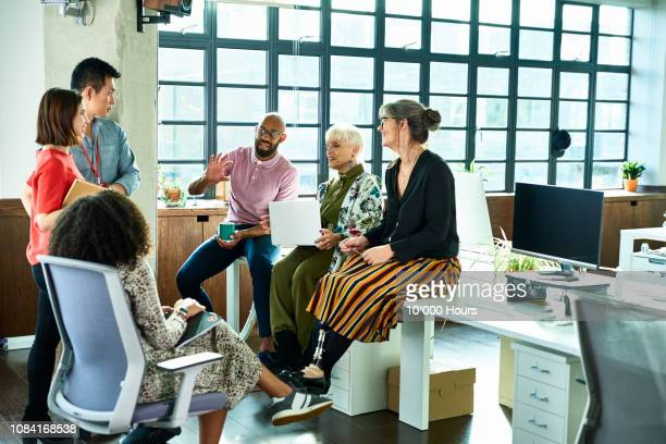 business colleagues in meeting with female amputee sitting on desk - multi etnische groep stockfoto's en -beelden
