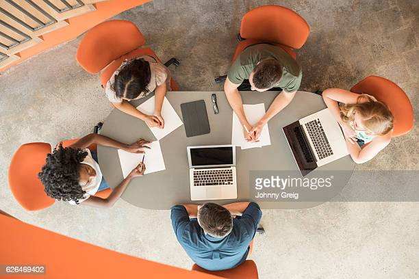 Business colleagues in meeting with laptops, overhead view
