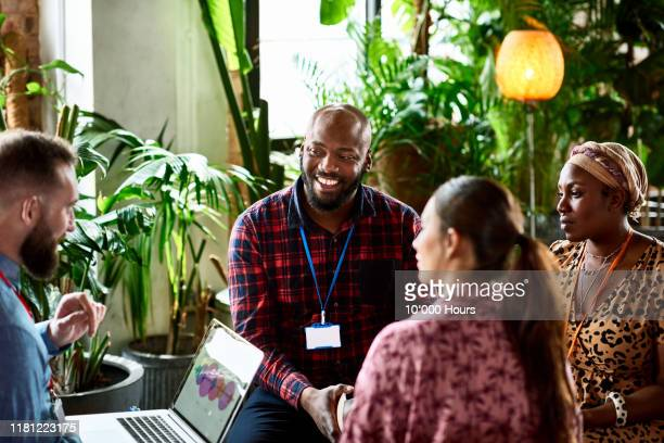 business colleagues in meeting with man using laptop - publicity event stock pictures, royalty-free photos & images