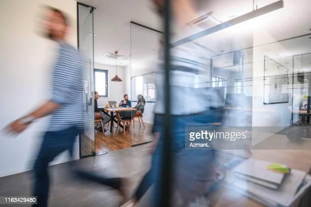 zakelijke collega's in beweging voorbij kantoor vergaderruimte - nieuw bedrijf stockfoto's en -beelden