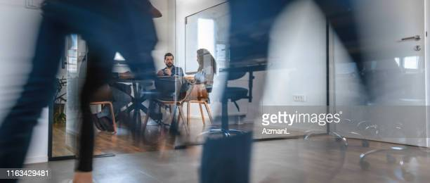 business colleagues in motion past office conference room - cooperation stock pictures, royalty-free photos & images