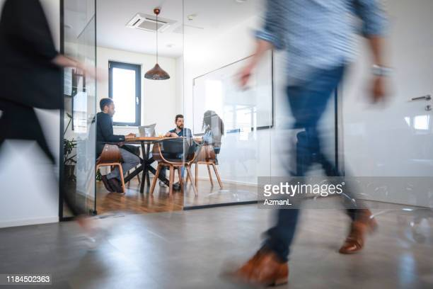 business colleagues in motion past office conference room - new business stock pictures, royalty-free photos & images