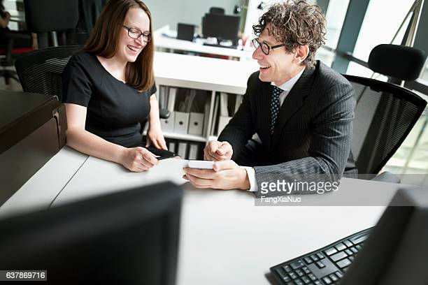 Business colleagues laughing together in design office