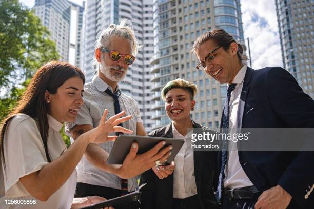 business colleagues laughing while looking at a digital tablet - alternative lifestyle stock pictures, royalty-free photos & images