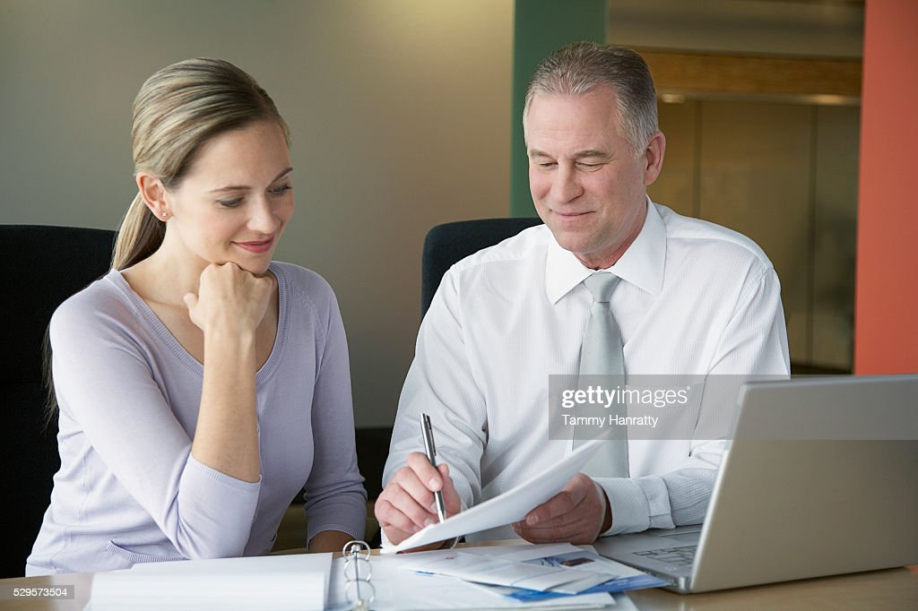 Business colleagues looking at documents : Stock Photo