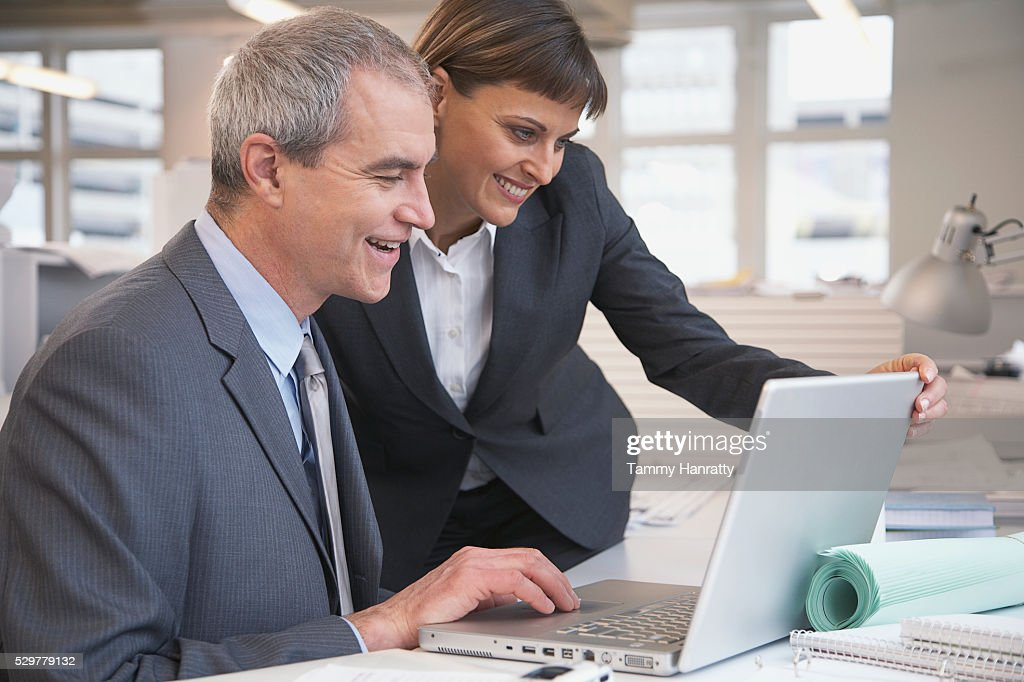 Business colleagues looking at laptop : Stock Photo