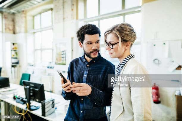 business colleagues looking at tablet together - striped shirt stock pictures, royalty-free photos & images