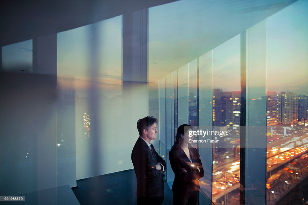 Business colleagues looking out window in office : ストックフォト