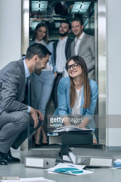 Business colleagues picking up dropped files and paperwork from the floor