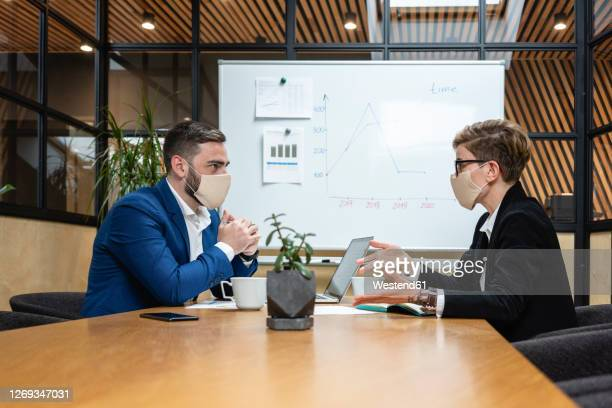 business colleagues planning strategy while sitting at desk in board room during coronavirus pandemic - interview stockfoto's en -beelden