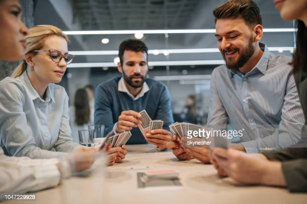 business colleagues playing cards on a break in the office. - poker card game stock photos and pictures