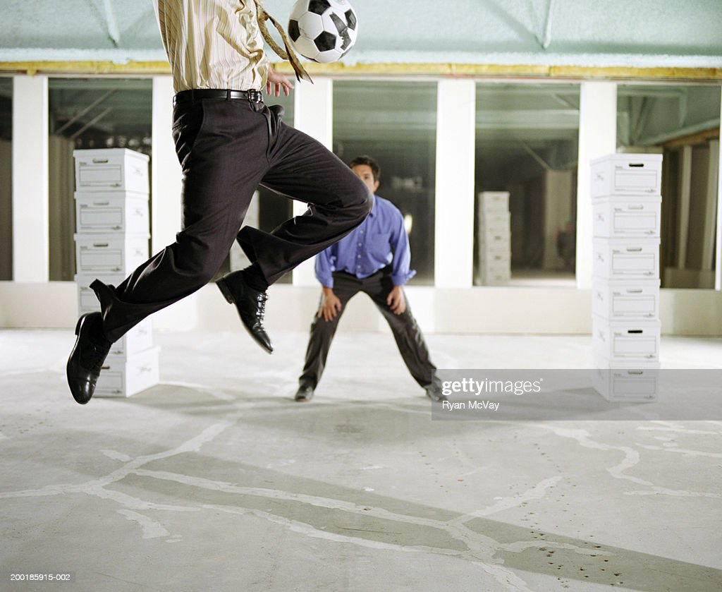 business colleagues playing soccer in empty office building stock photo