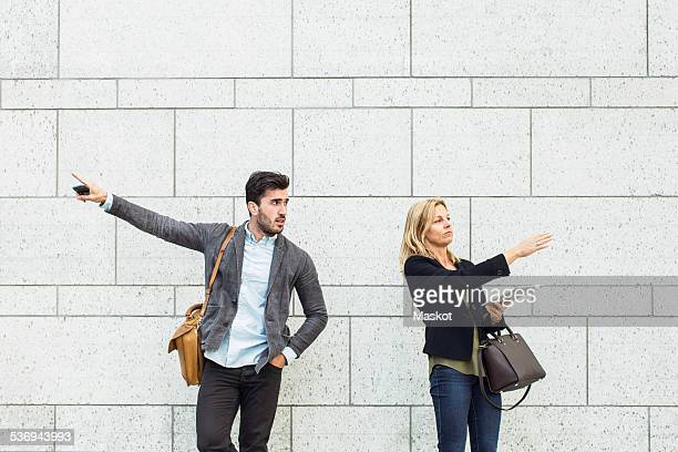 Business colleagues pointing opposite directions against wall outdoors