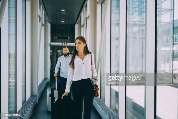 business colleagues pulling luggage while walking in corridor at airport - business travel stock pictures, royalty-free photos & images