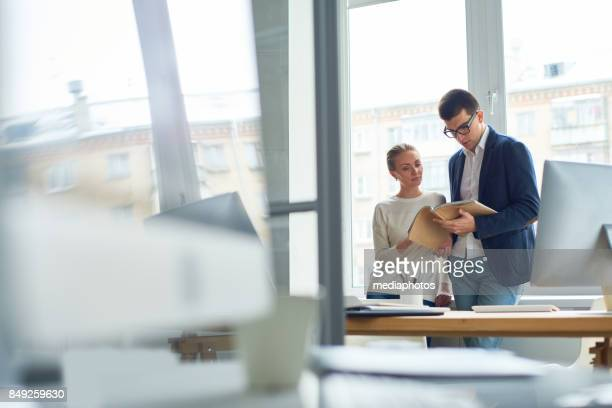 business colleagues reading handbook - handbook stock photos and pictures