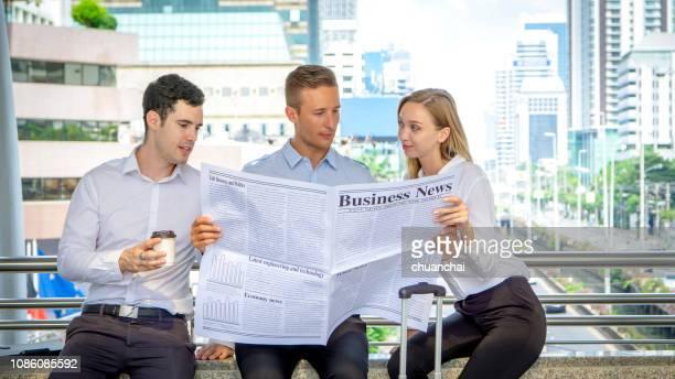 business colleagues reading newspaper while sitting on railing in city - écriture européenne photos et images de collection
