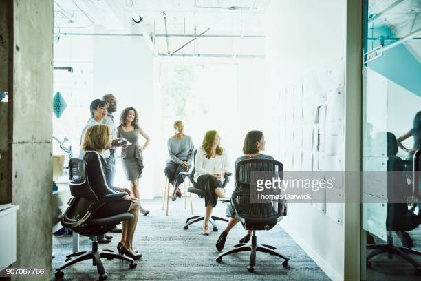 business colleagues reviewing and discussing project plans on office wall - improvement stock pictures, royalty-free photos & images