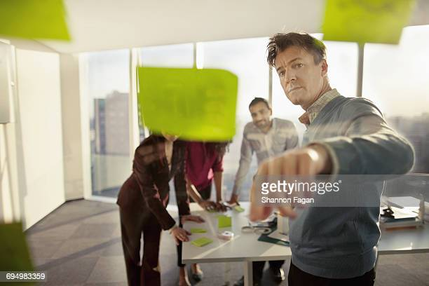 business colleagues reviewing ideas on glass wall - selective focus photos et images de collection