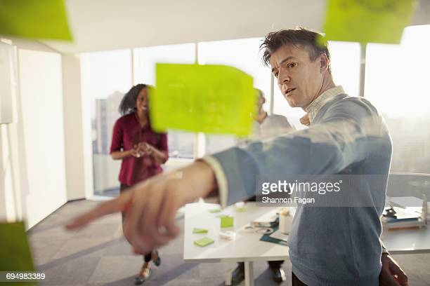 business colleagues reviewing ideas on glass wall - vanguardians stock pictures, royalty-free photos & images