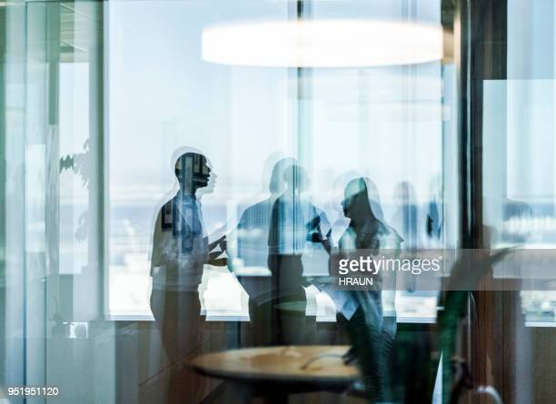 Business colleagues seen through glass at office