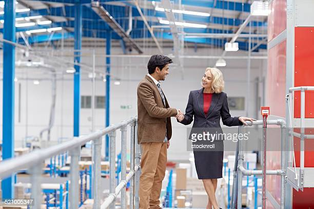 business colleagues shaking hands in factory - bezoek stockfoto's en -beelden