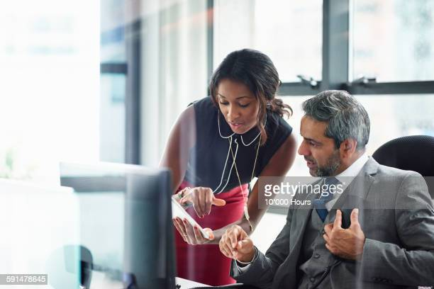business colleagues sharing information on an ipad - doing a favor stock pictures, royalty-free photos & images