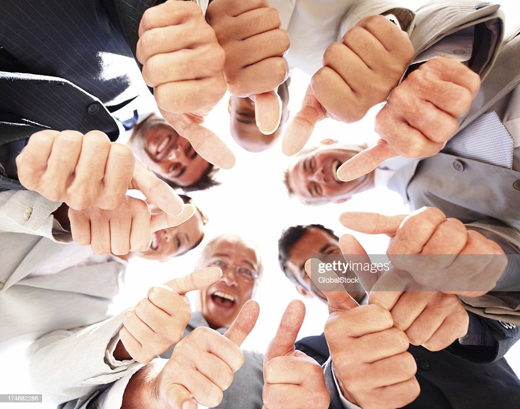 Business colleagues showing thumbs up sign : Stock Photo