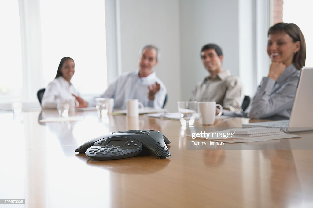 Business colleagues sitting at conference table : Stockfoto
