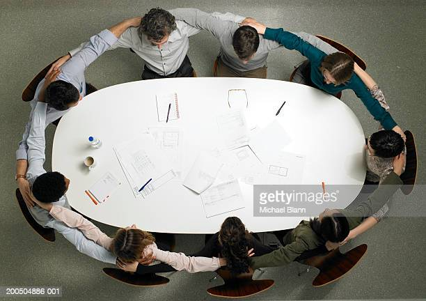 Business colleagues sitting at meeting table, arms around each other