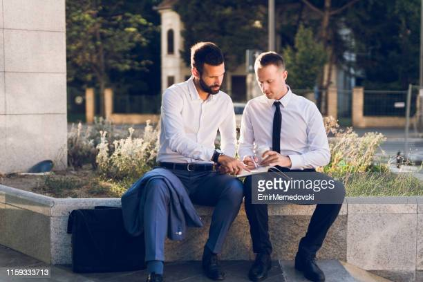 Business colleagues sitting on bench outdoors and collaborating