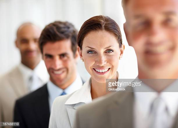 Business colleagues standing in a row whilst smiling