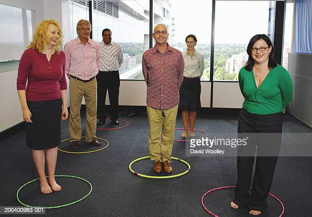 Business colleagues standing  plastic hoops, smiling