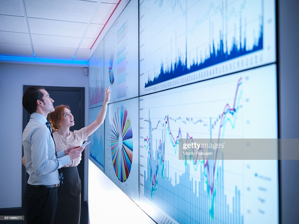 Business colleagues studying graphs on screen in meeting room : Foto de stock