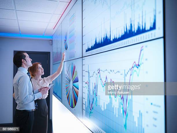 business colleagues studying graphs on screen in meeting room - calculating stock pictures, royalty-free photos & images