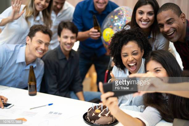 business colleagues taking a selfie at birthday party at work - anniversary stock pictures, royalty-free photos & images