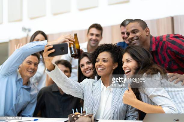 business colleagues taking a selfie at birthday party at work - happy hour stock pictures, royalty-free photos & images