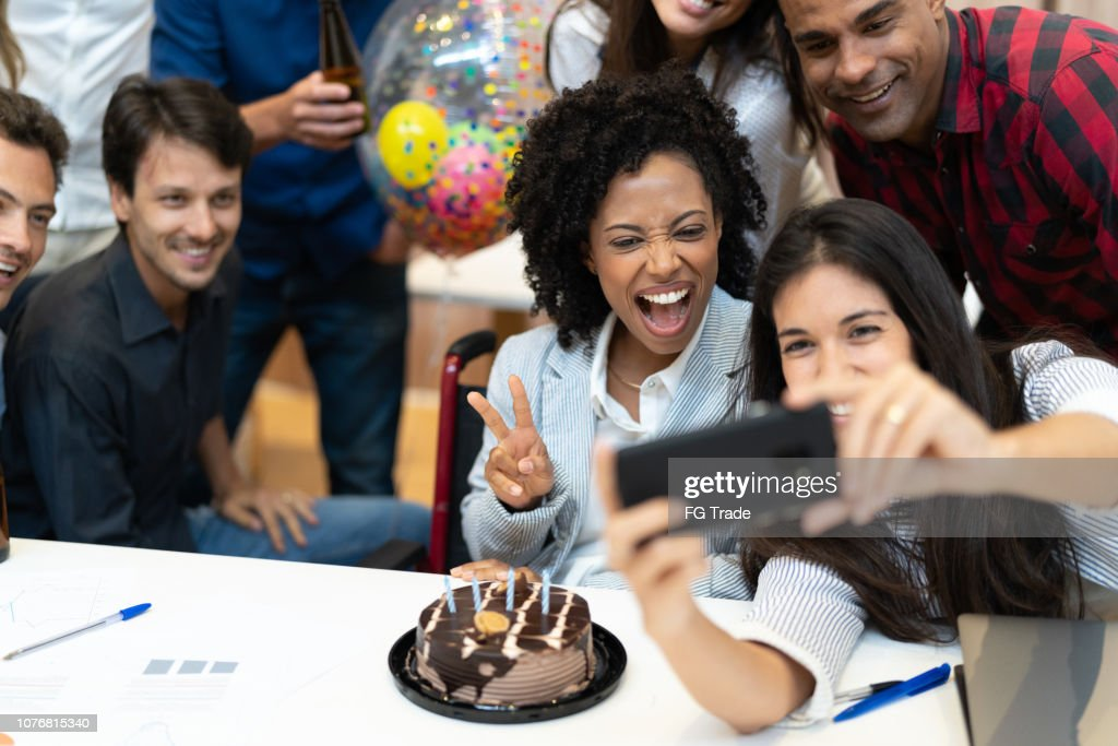 Business colleagues taking a selfie at birthday party at work : Stock Photo