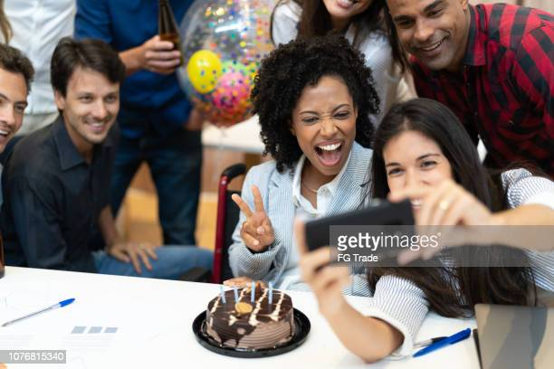 business colleagues taking a selfie at birthday party at work - work party stock pictures, royalty-free photos & images