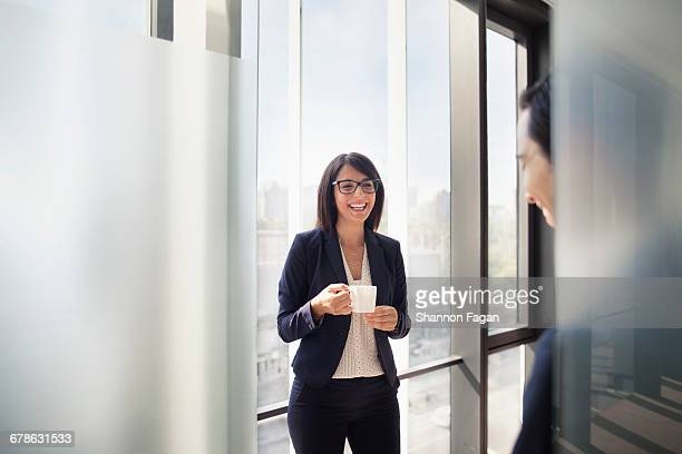 business colleagues talking and laughing in office - black blazer stock pictures, royalty-free photos & images