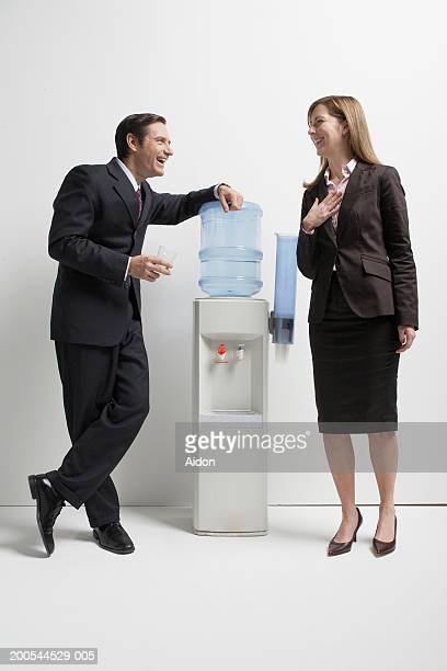Business colleagues talking by water cooler, studio shot