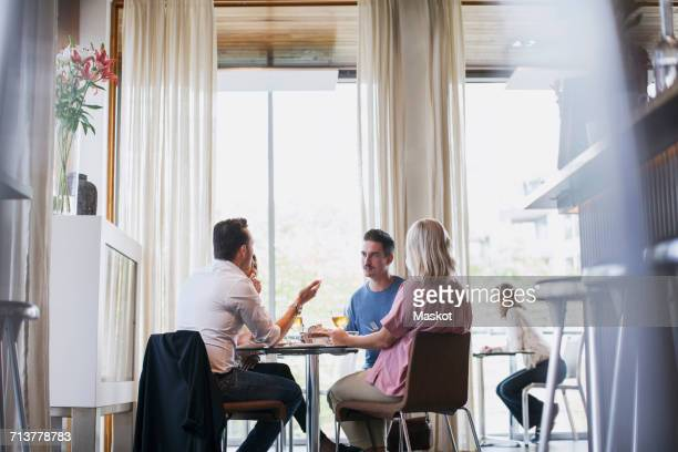 Business colleagues talking while eating lunch during meeting at restaurant