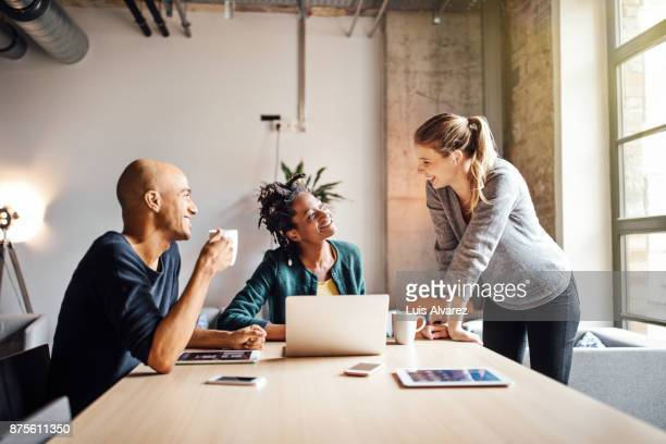 business colleagues talking while using laptop at office - new business stock pictures, royalty-free photos & images