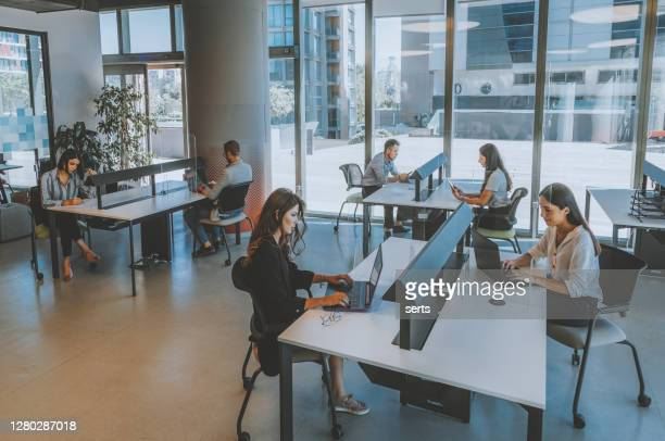 business colleagues team working behind acrylic glass sneeze by maintaining social distance in modern office during pandemic - health and safety stock pictures, royalty-free photos & images