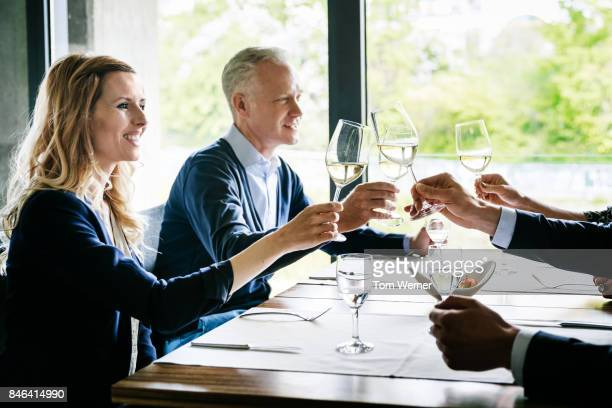 Business Colleagues Toasting Each Other Over Lunch At Restaurant.