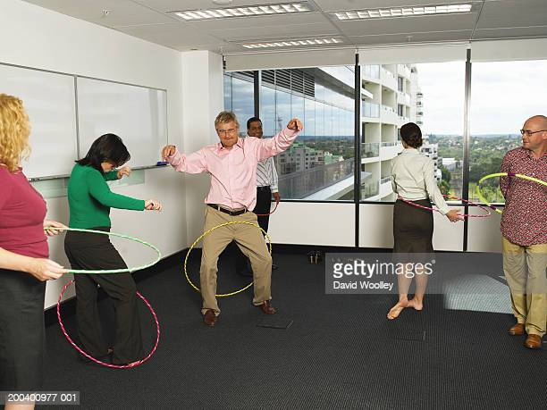 Business colleagues twirling plastic hoops