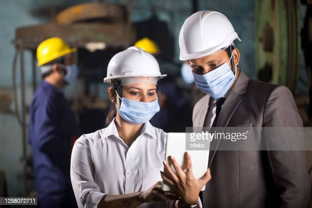 business colleagues using digital tablet at factory - labor union stock pictures, royalty-free photos & images
