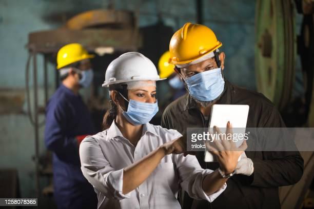 collègues d'affaires utilisant la tablette numérique à l'usine - prevention photos et images de collection