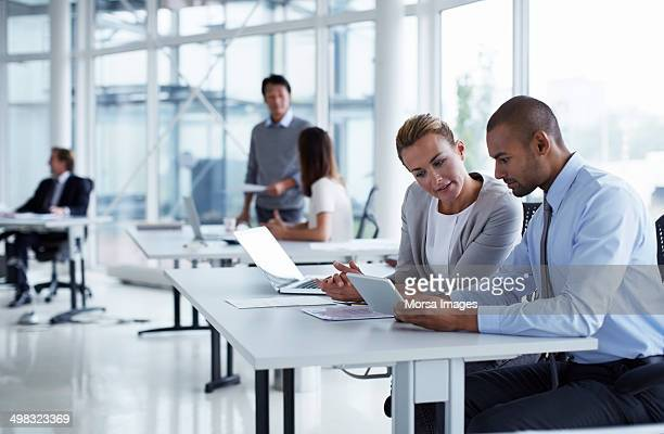 business colleagues using digital tablet - business plan stock pictures, royalty-free photos & images