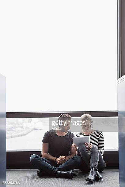 Business colleagues using digital tablet while sitting by window in office