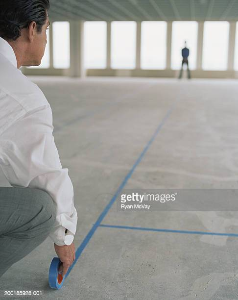 Business colleagues using tape to layout empty office space, rear view